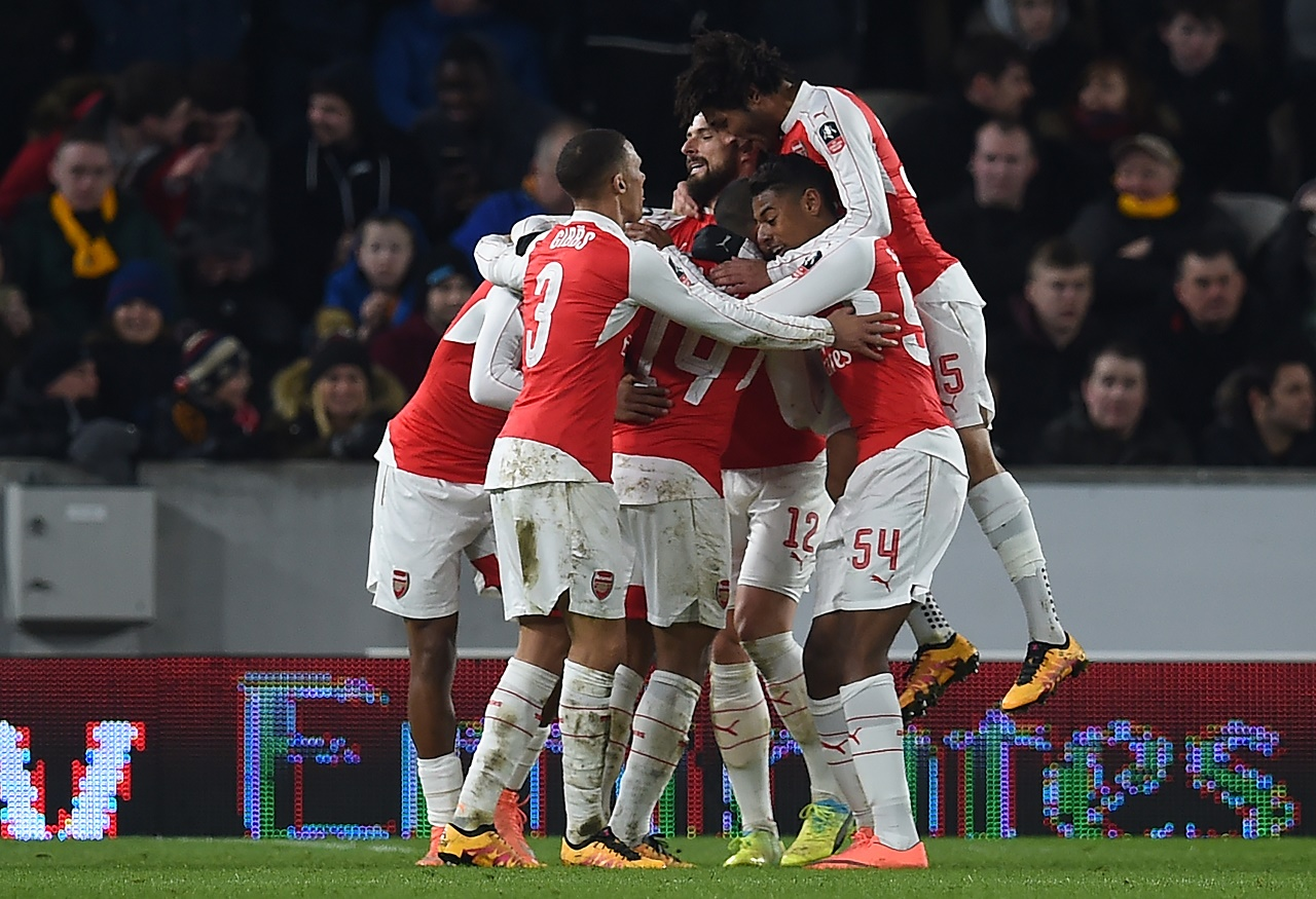 Arsenal's English midfielder Theo Walcott celebrates with teammates after scoring their third goal during the FA cup fifth round replay football match between Hull City and Arsenal at the KC Stadium in Kingston upon Hull in north east England on March 8, 2016.  / AFP / Paul ELLIS / RESTRICTED TO EDITORIAL USE. No use with unauthorized audio, video, data, fixture lists, club/league logos or 'live' services. Online in-match use limited to 75 images, no video emulation. No use in betting, games or single club/league/player publications.  /