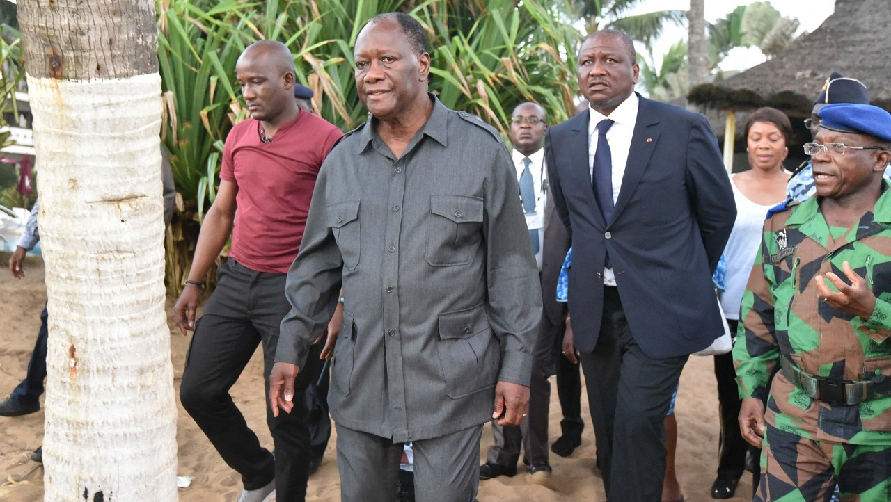 Ivorian president Alassane Ouattara (C) visits the beach resort of Grand-Bassam after gunmen went on a shooting rampage in three hotels, on March 13, 2016. Fourteen civilians and two soldiers were killed in the attack, President Alassane Ouattara said. / AFP / SIA-KAMBOU