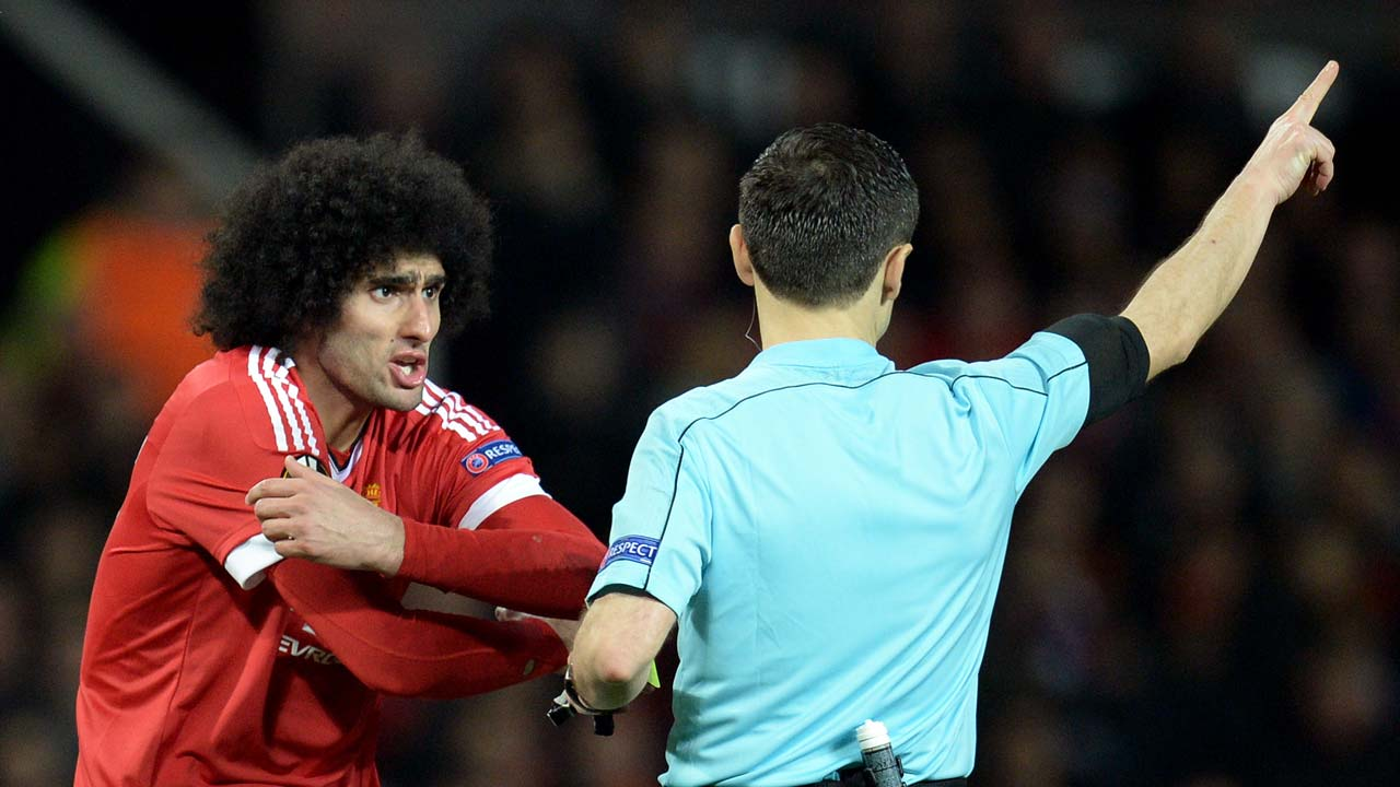 Serbian referee Milorad Mazic (R) speaks to Manchester United's Belgian midfielder Marouane Fellaini during the UEFA Europa League round of 16, second leg football match between Manchester United and Liverpool at Old Trafford in Manchester, north west England on March 17, 2016. OLI SCARFF / AFP