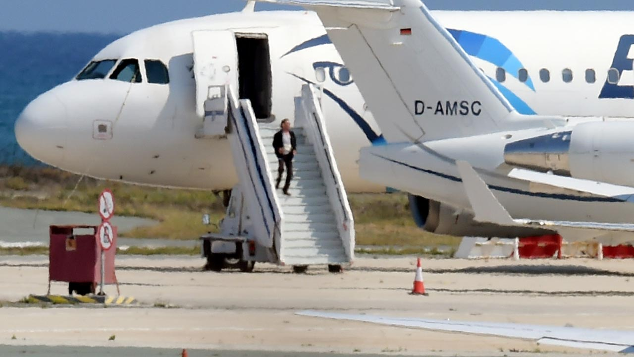 A man believed to be the hijacker of the EgyptAir Airbus A-320, which was diverted to Cyprus, leaves the plane before surrendering to security forces after a six-hour standoff on the tarmac at Larnaca airport's largely disused old terminal on March 29, 2016. The hijacker who seized the Egyptian airliner and forced it to land in Cyprus has been detained, Cypriot government spokesman Nicos Christodoulides said. GEORGE MICHAEL / AFP