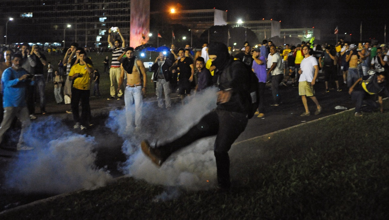 Demonstrators confront riot policemen as they protest against corruption in Brasilia on March 16, 2016. President Rousseff named her predecessor Luiz Inacio Lula da Silva as her chief of staff Wednesday, sparing him possible arrest for corruption as she seeks to fend off a damaging crisis. Ministerial immunity will now protect him from prosecution in ordinary court as cabinet ministers can only be tried before the Supreme Court in Brazil. AFP PHOTO/ANDRESSA ANHOLETE / AFP / Andressa Anholete