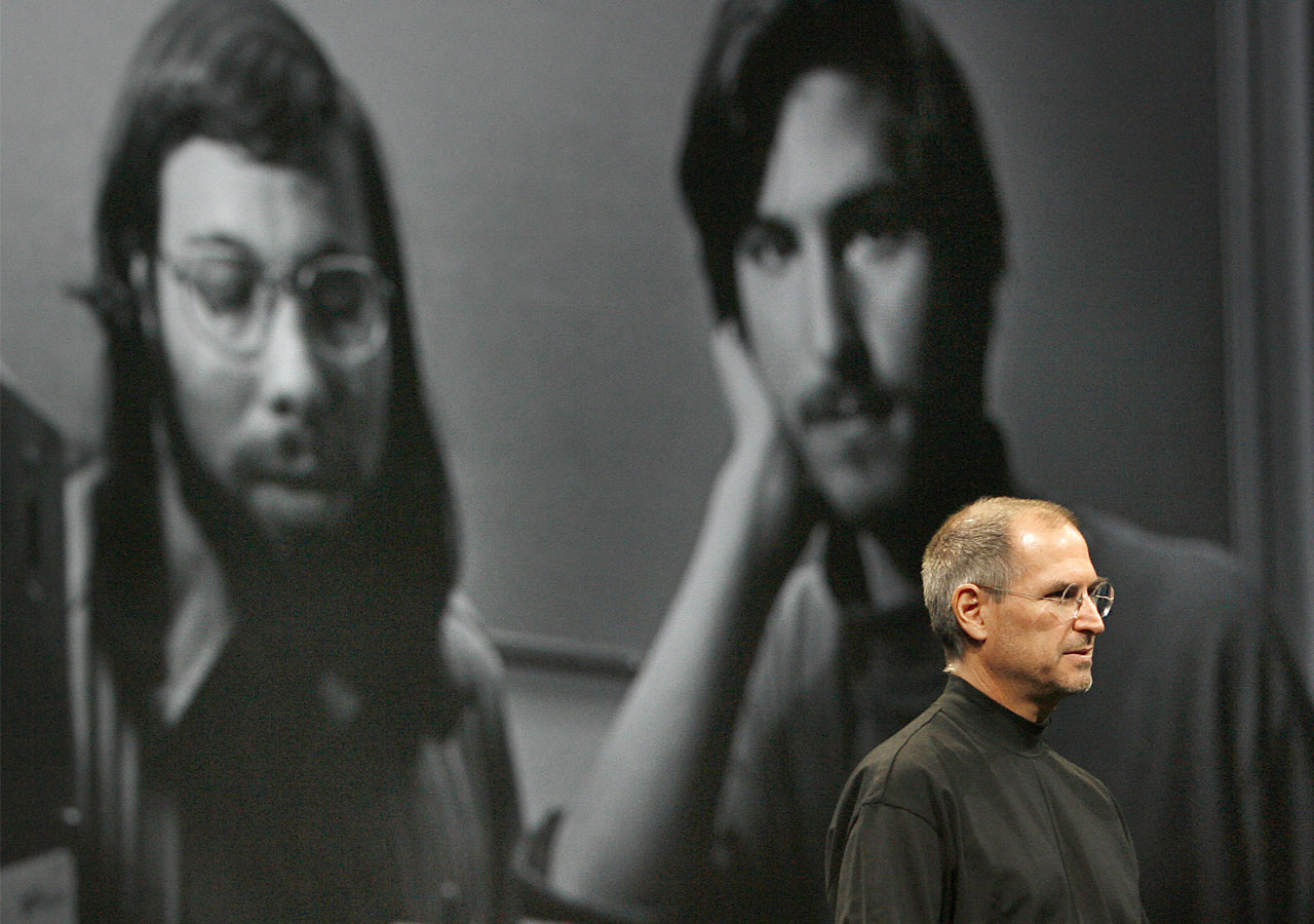 (FILES) This file photo taken on January 9, 2007 shows Apple chief executive Steve Jobs next to an old photo of Steve Wozniak (L) and himself when they first started Apple during the Macworld Conference in San Francisco. Apple celebrates its 40th anniversary this week at the top of its game, as the Silicon Valley legend that sprang out of Steve Jobs' garage to reshape modern life with its trend-setting gadgets. Jobs, the late tech-savvy marketing genius, and Steve Wozniak, who invented the Apple computer, helped revolutionize how people use technology, and formed what would become the world's largest corporation with an eye-popping $53 billion in annual profits. / AFP / TONY AVELAR