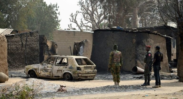Nigerian soldiers inspect a burnt vehicle following a suicide attack by the Boko Haram militant group in Maiduguri, on January 30, 2016. PHOTO: AFP