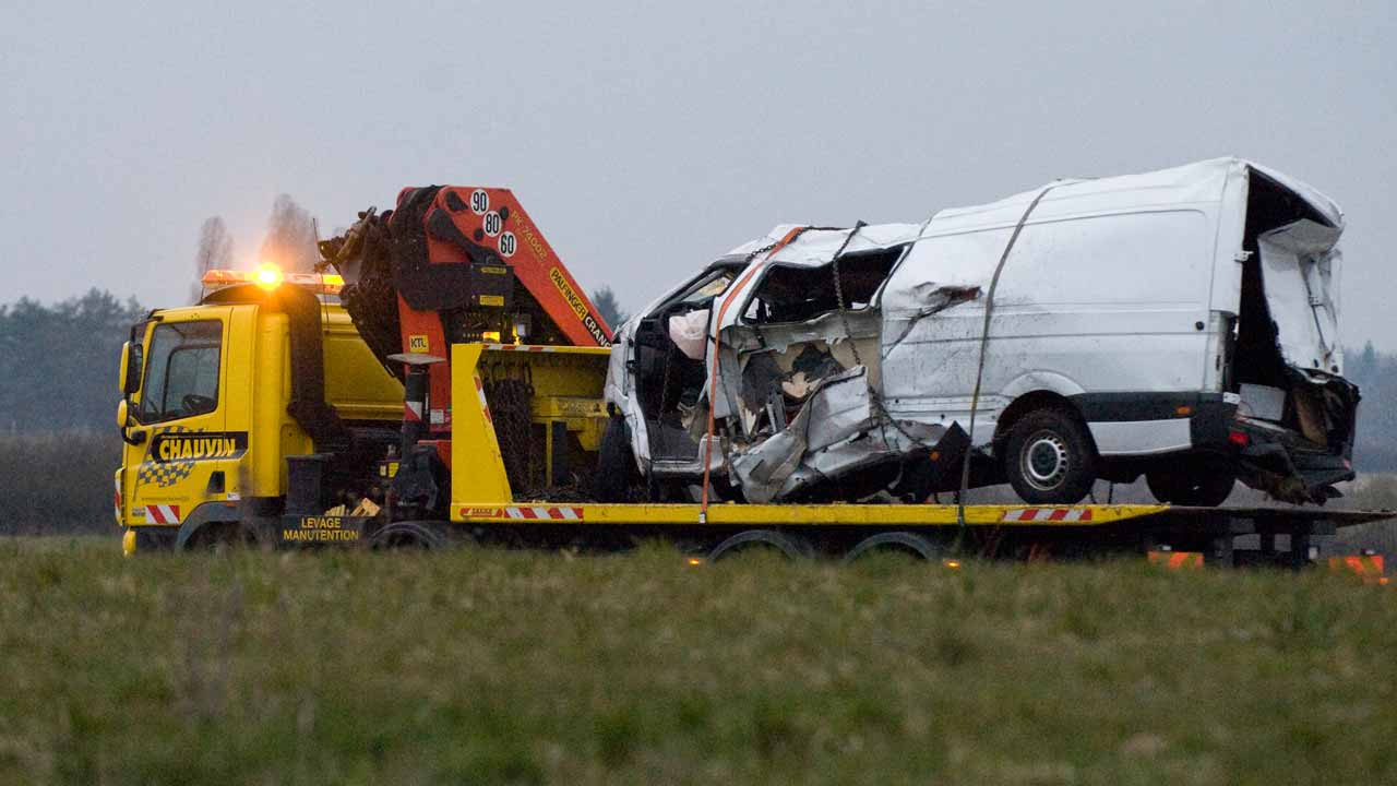 The wreckage of a minibus is being towed from an accident's site early on March 25, 2016 after it collided overnight with a truck in Montbeugny, central France. Twelve people were killed when the minibus they were travelling in collided with a heavy truck late March 24 in Allier, central France, local authorities said. Thierry Zoccolan / AFP