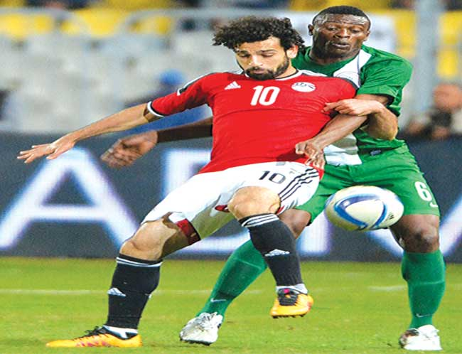 Super Eagles' Stanley Amuzie (left) tries to stop Egypt's Mohamed Salah during their African Cup of Nations Group G match at the Borg el-Arab Stadium in Alexandria… on Tuesday. PHOTO: AFP