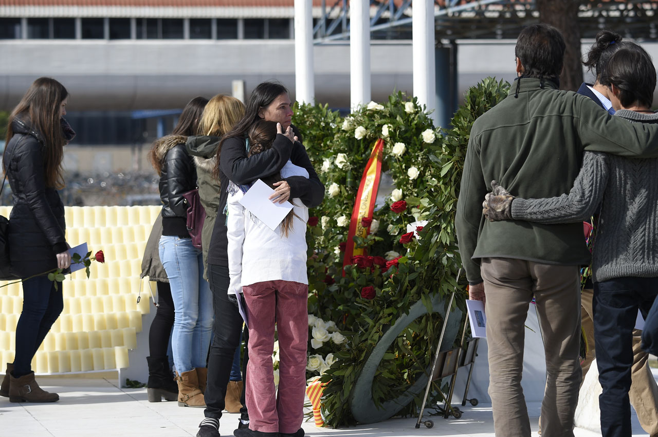 Relatives of the victims of the Germanwings crash pay tribute and react next to the commemorative plaque set for the victims of the Germanwings plane which crashed into the French Alps and claimed 150 lives, at Barcelona's airport, in El Prat de Llobregat on March 23, 2016. The crash killed all 144 passengers and six crew -- a group of people from 20 countries, among them 72 Germans and 50 Spaniards, heading back from Barcelona and bound for Duesseldorf airport. / AFP / LLUIS GENE