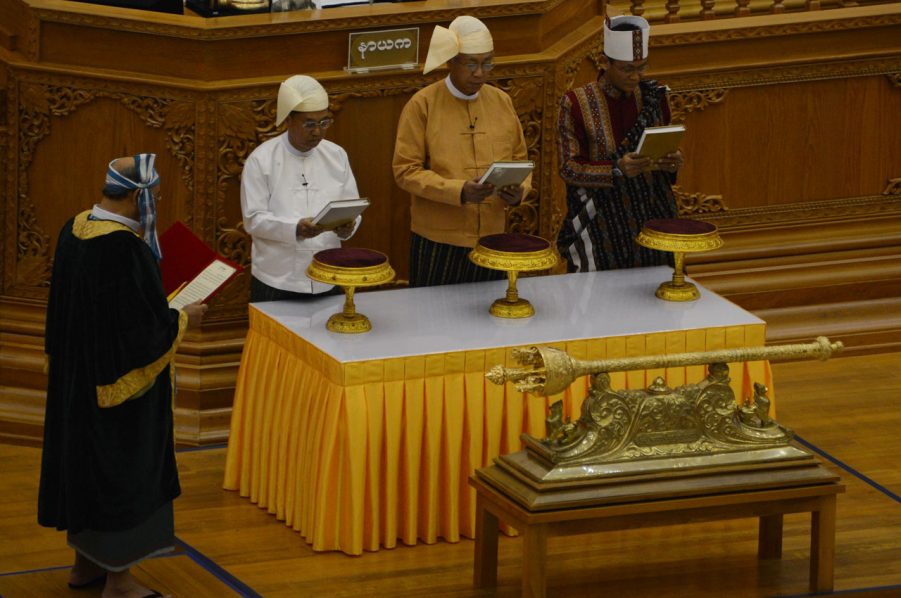 Myanmar new President Htin Kyaw (3L), flanked by Vice Presidents Myint Swe (2L) and Henry Van Thio (4L), is sworn in by House Speaker Mahn Win Khine Than (1L) during a ceremony in Naypyidaw on March 30, 2016. A close aide to Aung San Suu Kyi was sworn in as Myanmar's president on March 30, a role that will see him act as a proxy for the pro-democracy figurehead and carry the hopes of a nation emerging from military rule. / AFP / ROMEO GACAD