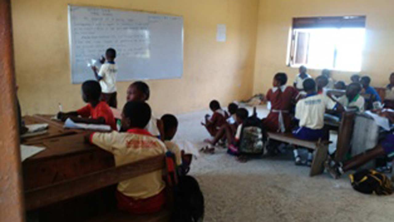 Pupils sitting haphazardly in class due to inadequate chairs and desks