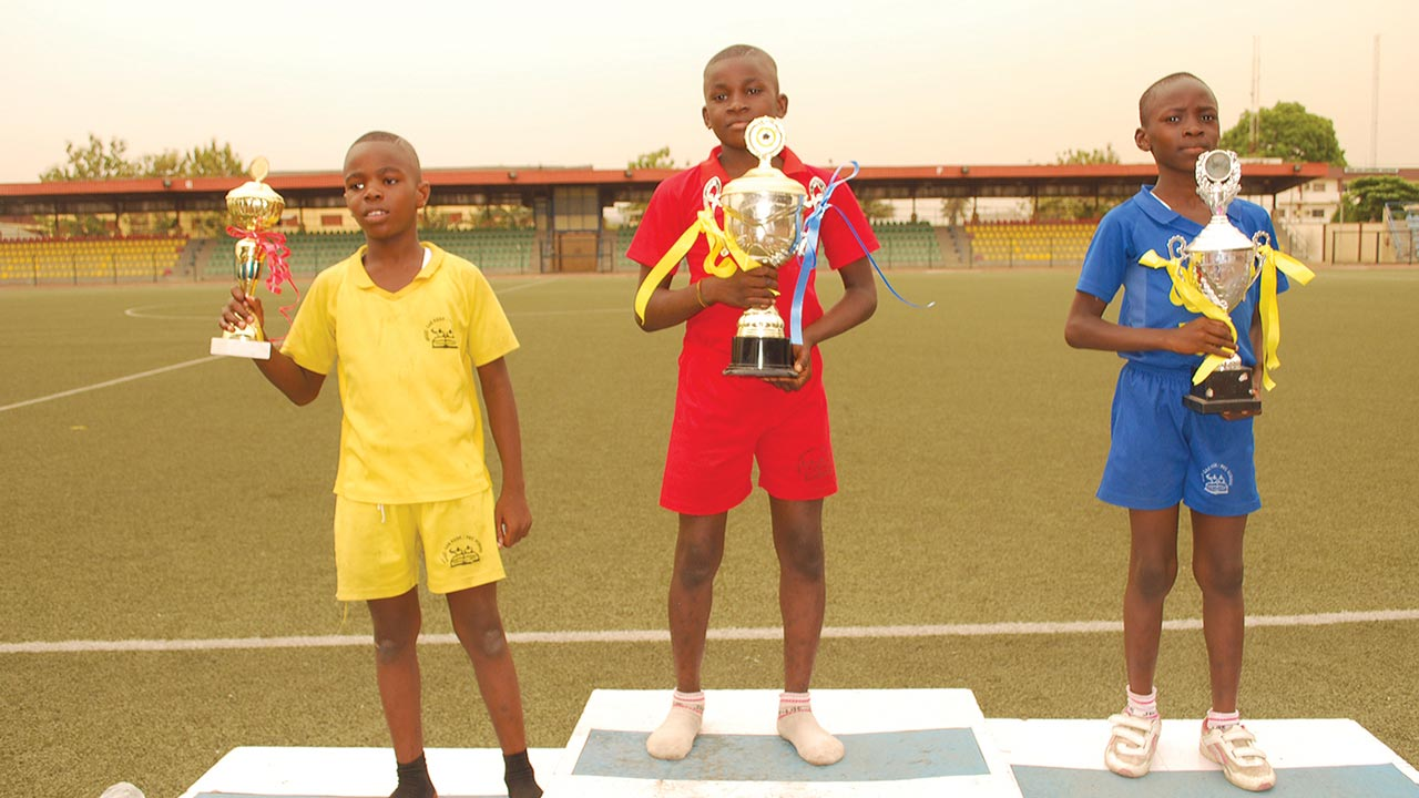 Yellow House Captain, Kareem Bashorun (left), his counterparts from Red and Blue houses, Sunday Chikwenye and Samad Oyetunji, displaying their trophies during the Jelly-Las Schools Inter-House Sports competition at the Agege Stadium, Lagos.