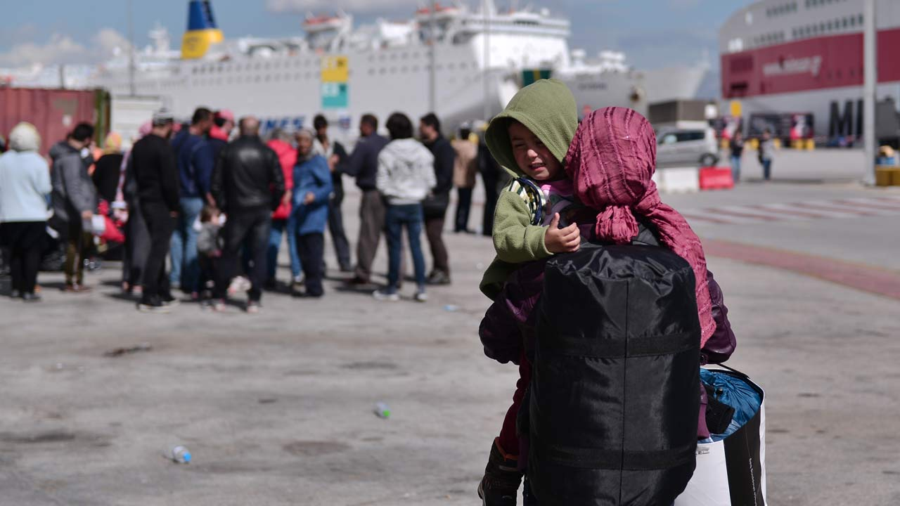 A woman migrant carrying her son in the port of Piraeus on March 10, 2016, waits to be transferred to a refugee camp in central Greece with other migrants and refugees. Greek authorities began transporting hundreds of migrants and refugees, stranded in Piraeus port to shelters in central Greece . Some 42,000 people are stranded in Greece following border restrictions and closures by Austria and several Balkan countries. LOUISA GOULIAMAKI / AFP