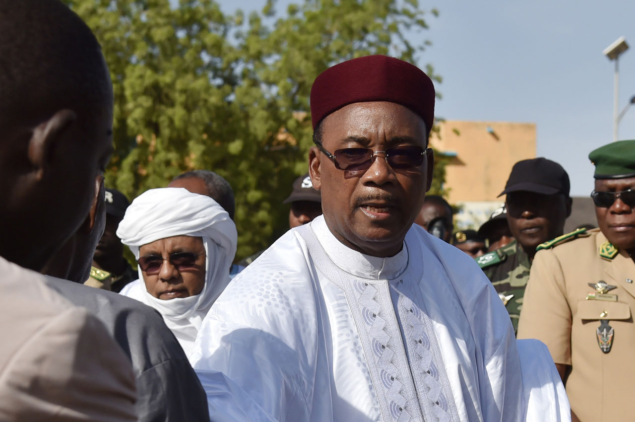 Niger's President Mahamadou Issoufou (C) attends the funeral ceremony of an army commander killed by Boko Haram in the Diffa region, near the border with Nigeria, in Niamey on March 19, 2016. Four suicide bombers attacked a military convoy, killing the local military commander and injuring two others on March 18, just days before the impoverished west African nation votes in the second round of presidential elections. / AFP / ISSOUF SANOGO