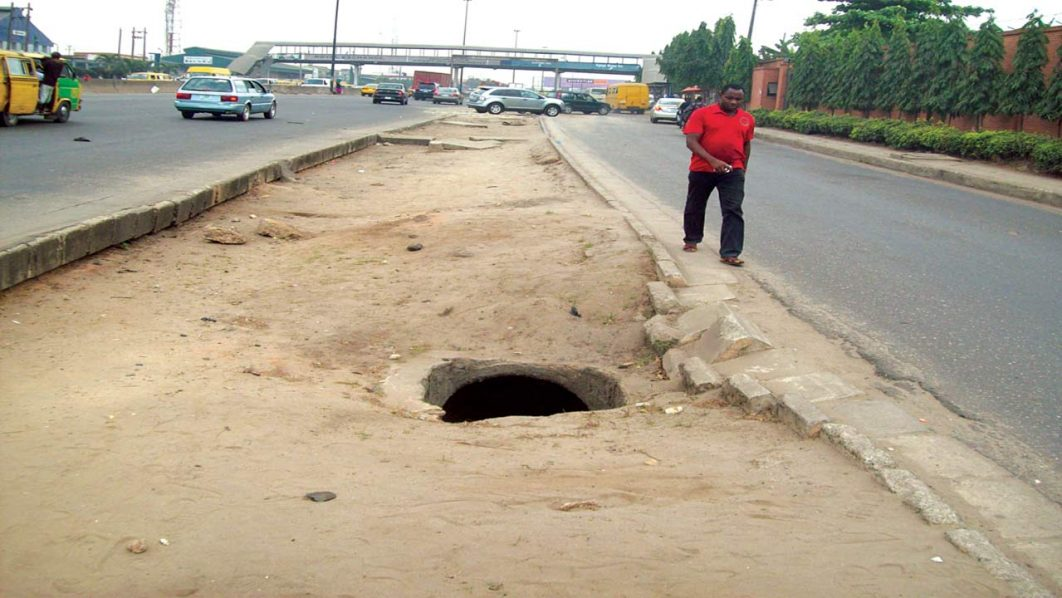 A pedestrian walks past a manhole at Charity bus stop, along Oshodi-Isolo expressway PHOTO: PAUL ADUNWOKE