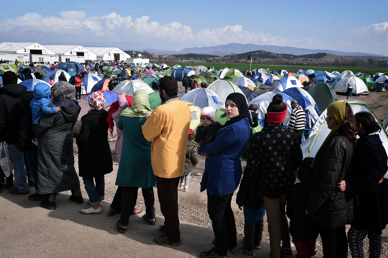 People queue for food in the makeshift migrant camp at the Greek-Macedonian border near the Greek village of Idomeni, on March 2, 2016 , where thousands of people are stranded. The European Union on March 2 unveiled a 700-million-euro emergency aid plan for Greece and other states hit by the migrant crisis, in what would be the first time humanitarian cash has been used within Europe instead of outside the bloc. The United Nations has warned of a looming humanitarian crisis as thousands of refugees are stuck in wintry misery at the Greece-Macedonia border after a domino effect of Balkan border closures. / AFP / LOUISA GOULIAMAKI