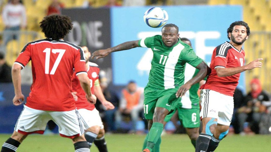 Egypt's Marwan Mohsen (right) watches on as Nigeria's Victor Moses heads the ball during their African Cup of Nations group G qualification football match at the Borg el-Arab Stadium in Alexandria… on Tuesday. PHOTO: AFP.