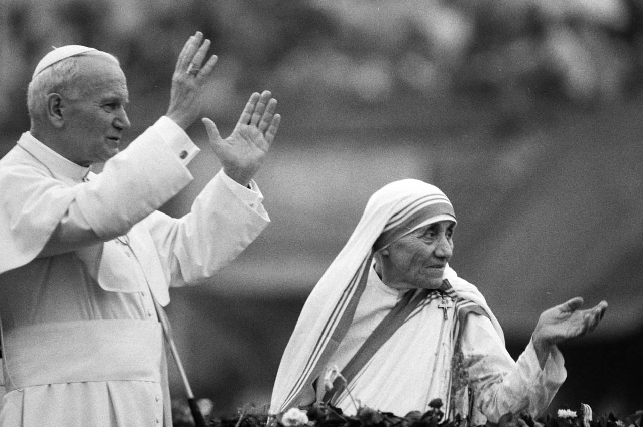 (FILES) This file photo taken on February 03, 1986 shows Mother Teresa and Pope John Paul II waving to well-wishers, at the Nirmal Hriday Home, in Calcutta. The Vatican committee that approves elevations to sainthood will meet on March 15, 2016 to consider a recommendation that Mother Teresa of Calcutta becomes Saint Theresa, the Holy See announced on March 14, 2016. / AFP / JEAN-CLAUDE DELMAS