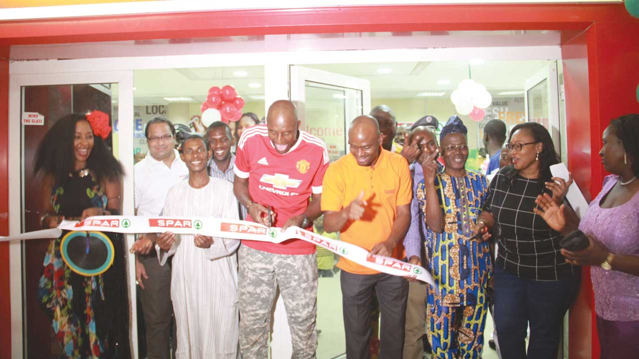 John Fashanu ( middle) unveiling the store in Abuja