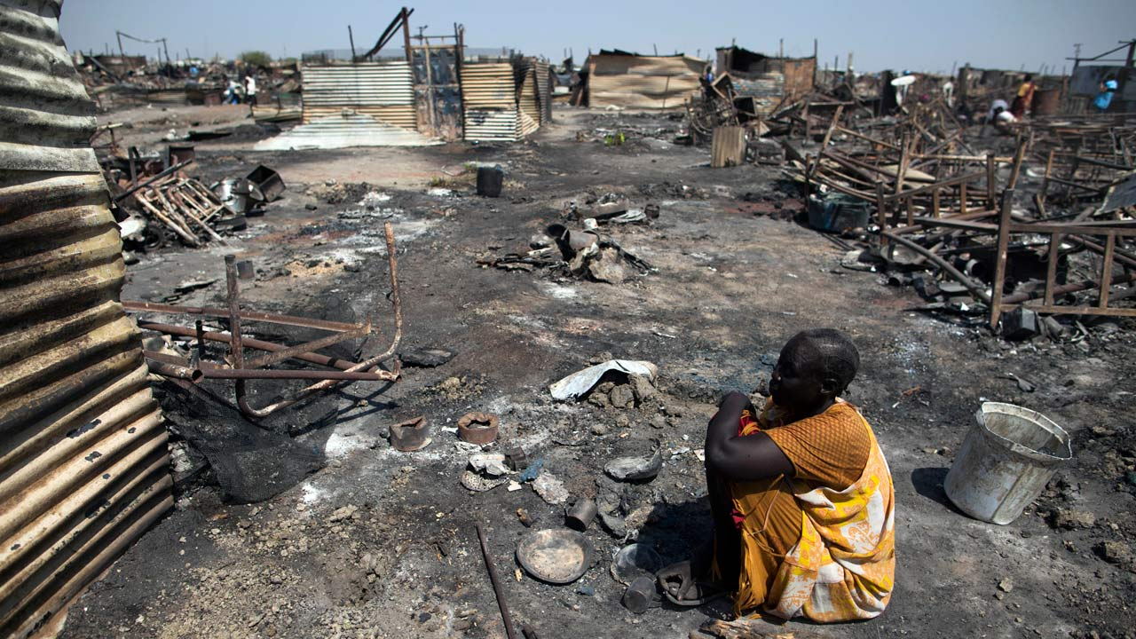 (FILES) This file photo taken on February 26, 2016 shows Akki Adduok, a displaced woman residing in the Protection of Civilians (PoC) site in Malakal, South Sudan, sitting in the spot where her shelter used to be. At least 25 people were massacred and 120 wounded when gunmen in army uniforms attacked then torched a UN camp that was sheltering civilians in South Sudan last month, the UN said on March 4, 2016. The updated toll comes two weeks after the two-day gun battle inside the camp in the northeastern town of Malakal, with a report by the UN Office for the Coordination of Humanitarian Affairs (OCHA) detailing the failure of peacekeepers to protect the civilians sheltering at the base. Over 47,000 people lived in the camp, after fleeing for safety from a civil war that broke out in December 2013. The UN has said the attack was a possible war crime. Albert Gonzalez Farran / AFP