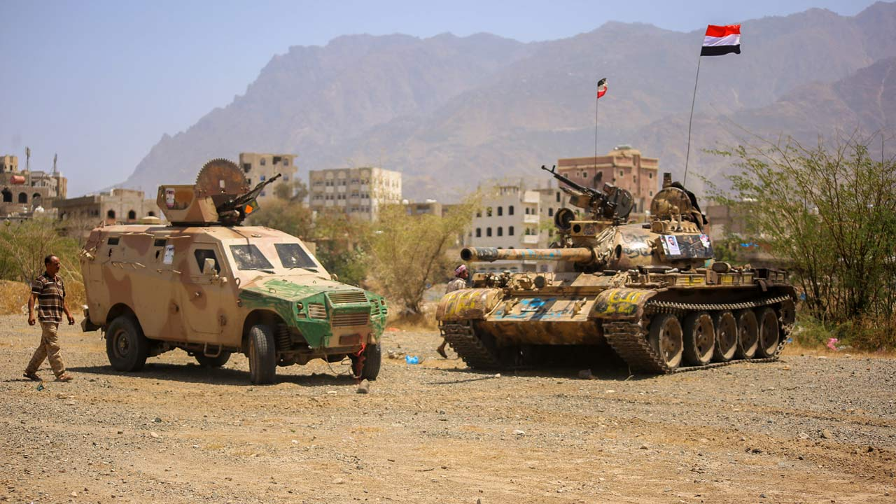 A Yemeni man walks past military vehicles at the headquarters of the army's 35th brigade, in the western suburbs of Taez, after forces loyal to Yemen's Saudi-backed president pushed back Huthi rebels and their allies trying to retake the area on March 12, 2016. AHMAD AL-BASHA / AFP