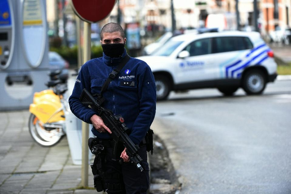 A Belgian police officer stands guard during an anti-terror raid in the Schaerbeek - Schaarbeek district of Brussels, on March 25, 2016 (AFP Photo/Patrik Stollarz)