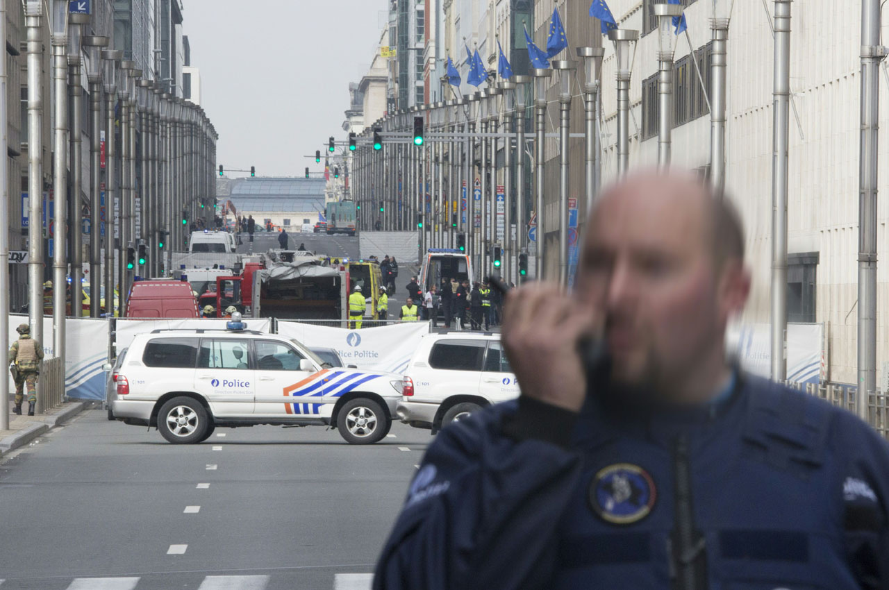 A police officer stands guard near a security perimeter set in the Rue de la Loi near the Maalbeek subway station, in Brussels, on March 22, 2016, after an explosion killed around 10 people, according to spokesman of Brussels' fire brigade  A string of explosions rocked Brussels airport and a city metro station on Tuesday, killing at least 13 people, according to media reports, as Belgium raised its terror threat to the maximum level. / AFP / Belga / HATIM KAGHAT / Belgium OUT