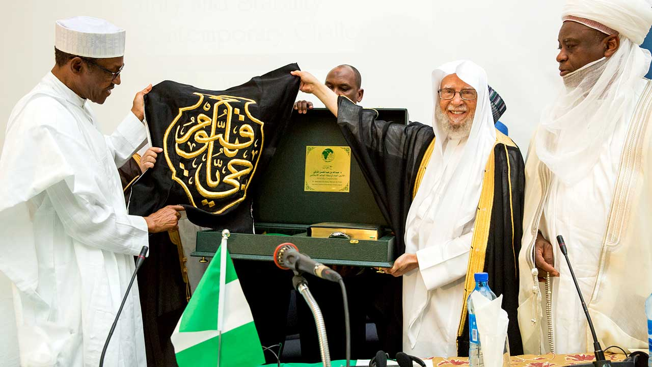 Islamic Conference 3: President Buhari receiving a gift presentation from the Executive Secretary World Muslim League Saudi Arabia Dr Abdullah Bin Abdul Mohsin Al-Turki, with him is Sultan of Sokoto Alhaji Sa'ad Abubakar as President Buhari declares open the International Islamic Conference on Peace and Security at the Shehu Yar'Adua Centre Abuja on 17th Mar 2016