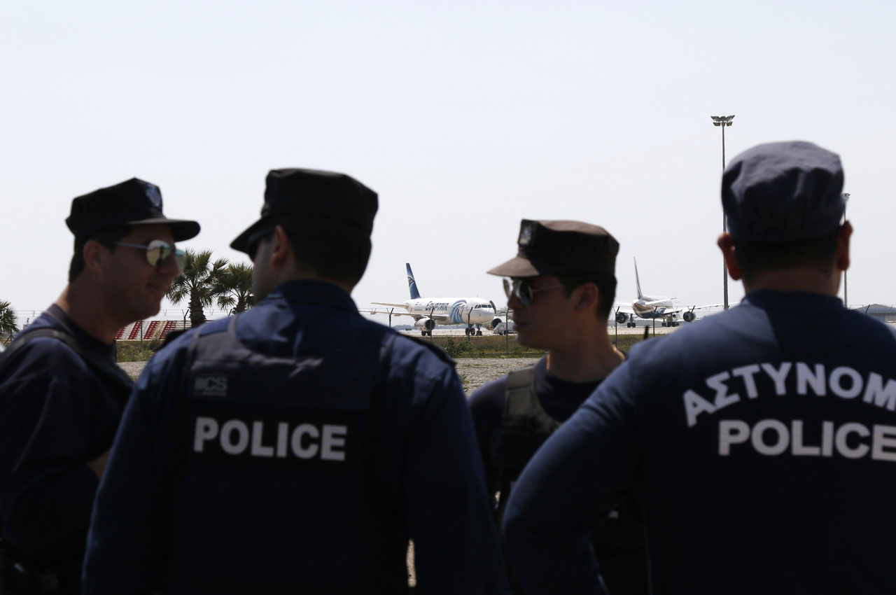 Cypriot policemen stand guard in the vicinity of Larnaca airport where an EgyptAir Airbus A-320 (C) sits on the tarmac after being hijacked and diverted to Cyprus on March 29, 2016.  A hijacker seized an Egyptian airliner and forced it to land in Cyprus, but nearly all of the passengers were quickly released and officials said the incident was not linked to terrorism. / AFP / BEHROUZ MEHRI