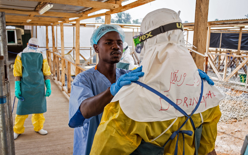 A health care worker prepares a colleague's Ebola virus protective gear at an Ebola virus clinic operated by the International Medical Corps in Makeni, Sierra Leone. Photo: AP