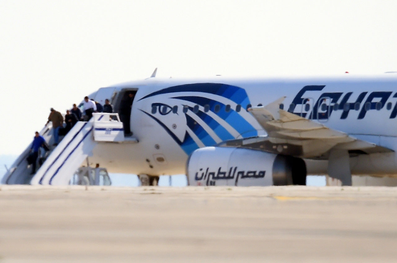 Passengers disembark an EgyptAir Airbus A-320 sitting on the tarmac of Larnaca aiport after it was hijacked and diverted to Cyprus on March 29, 2016. A hijacker seized the Egyptian airliner and diverted it to Cyprus, before releasing all the passengers except four foreigners and the crew, officials and the airline said. / AFP / GEORGE MICHAEL
