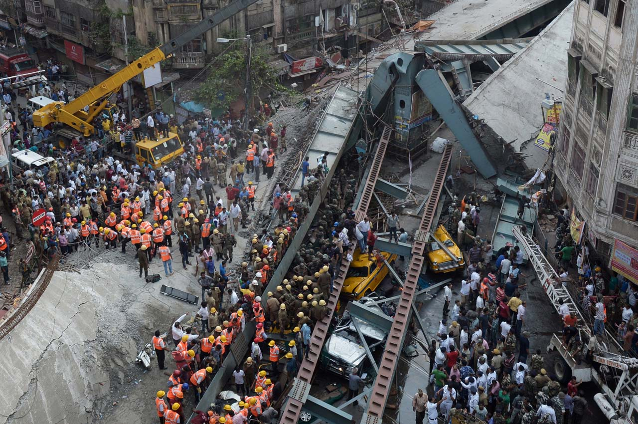Indian rescue workers and volunteers try to free people trapped under the wreckage of a collapsed fly-over bridge in Kolkata on March 31, 2016. At least 14 people were killed and dozens more injured when a flyover collapsed in a busy Indian city on March 31, an official said, as emergency workers battled to rescue people trapped under the rubble.  / AFP / Dibyangshu SARKAR