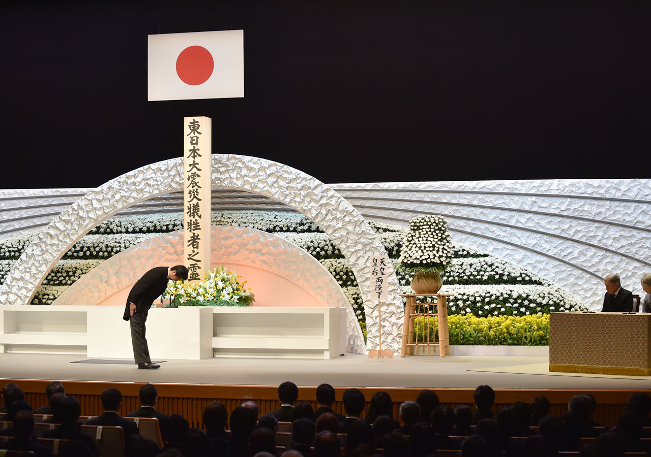 Japanese Prime Minsiter Shinzo Abe (L) bows to Emperor Akihito (2nd R) and Empress Michiko (R) in front of an altar for the victims of the March 11, 2011 earthquake and tsunami at the national memorial service in Tokyo on March 11, 2016. Japan paused on March 11 to mark five years since an offshore earthquake spawned a monster tsunami that left about 18,500 people dead or missing along its northeastern coast. / AFP / POOL / POOL / KAZUHIRO NOGI