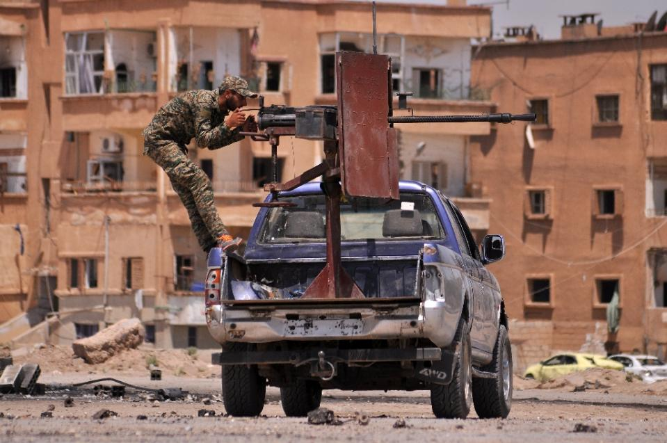 A member of the Kurdish People's Protection Units (YPG) mans a mounted machine gun in the Al-Nashwa neighbourhood in the northeastern Syrian province of Hasakeh on July 26, 2015 (AFP Photo/Delil Souleiman)