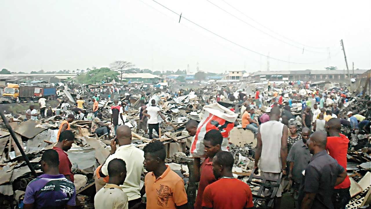 Traders in last minute rush to pick their wares after the demolition by unknown persons... yesterday.