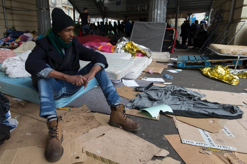 A migrant sits on a mattress at a makeshift camp in Paris on March 24, 2016 (AFP Photo/Joel Saget)