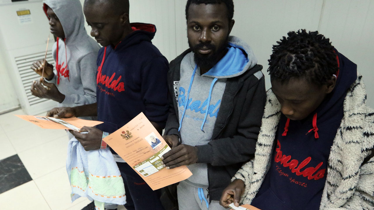 Migrants hold their emergency certificates at the Metiga Airport in the Libyan capital Tripoli on March 11, 2016 ahead of their repatriation to their countries of origin by the Libyan authorities. The formalities for their departure were organised by the Libyan authorities and the mission of the International Organisation for Migration (IOM). Before embarking, their personal belongings, which were confiscated at the time of their arrest, were returned alongside a boarding pass. / AFP / MAHMUD TURKIA