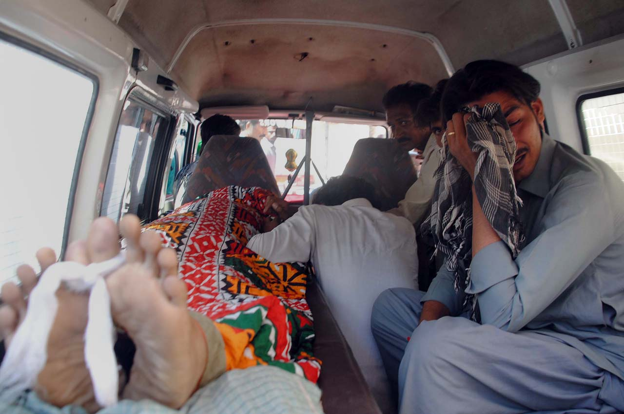 Pakistani relatives react as they sit alongside the body of a family member who died after drinking tainted alcohol in an ambulance in Hyderabad on March 22, 2016. At least 15 people including two women died in a southern Pakistani town after drinking tainted liqour, with many more being treated in hospital, police said. / AFP / Yousuf Nagori