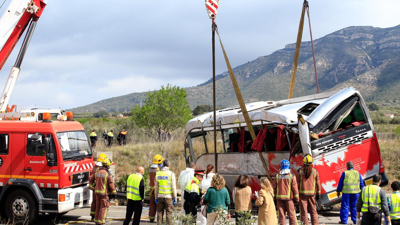 "Emergency personnel stand as a crane rights a bus on the Spanish AP-7 motorway near Freginals, Amposta south of Tarragona following a fatal accident that claimed the lives of 13 foreign students an injured 44 others early on March 20, 2016. The students, enrolled at Barcelona University as part of the European Erasmus exchange programme, were returning from a traditional festival in the eastern city of Valencia when the driver ""hit the railing on the right and swerved to the left so violently that the bus veered onto the other side of the highway,"" Jordi Jane,who heads interior matters for the Catalonia region, said. PAU BARRENA / AFP"