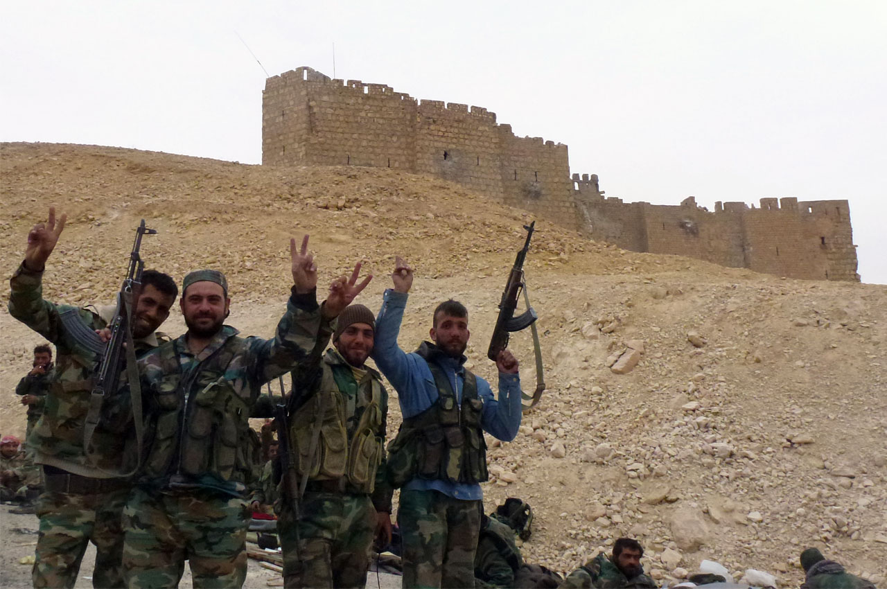 Syrian pro-governement forces gesture next to the Palmyra citadel on March 26, 2016, during a military operation to retake the ancient city from the jihadist Islamic State (IS) group. / AFP / Maher AL MOUNES