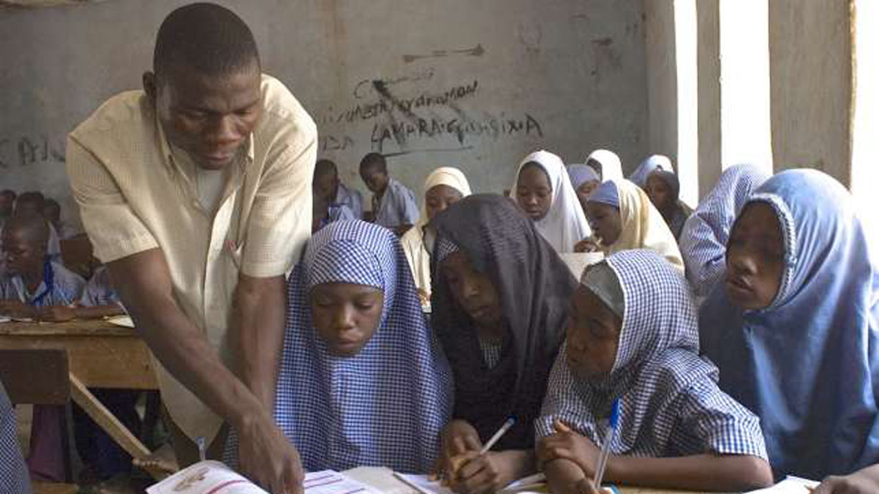 A teacher attends to pupils