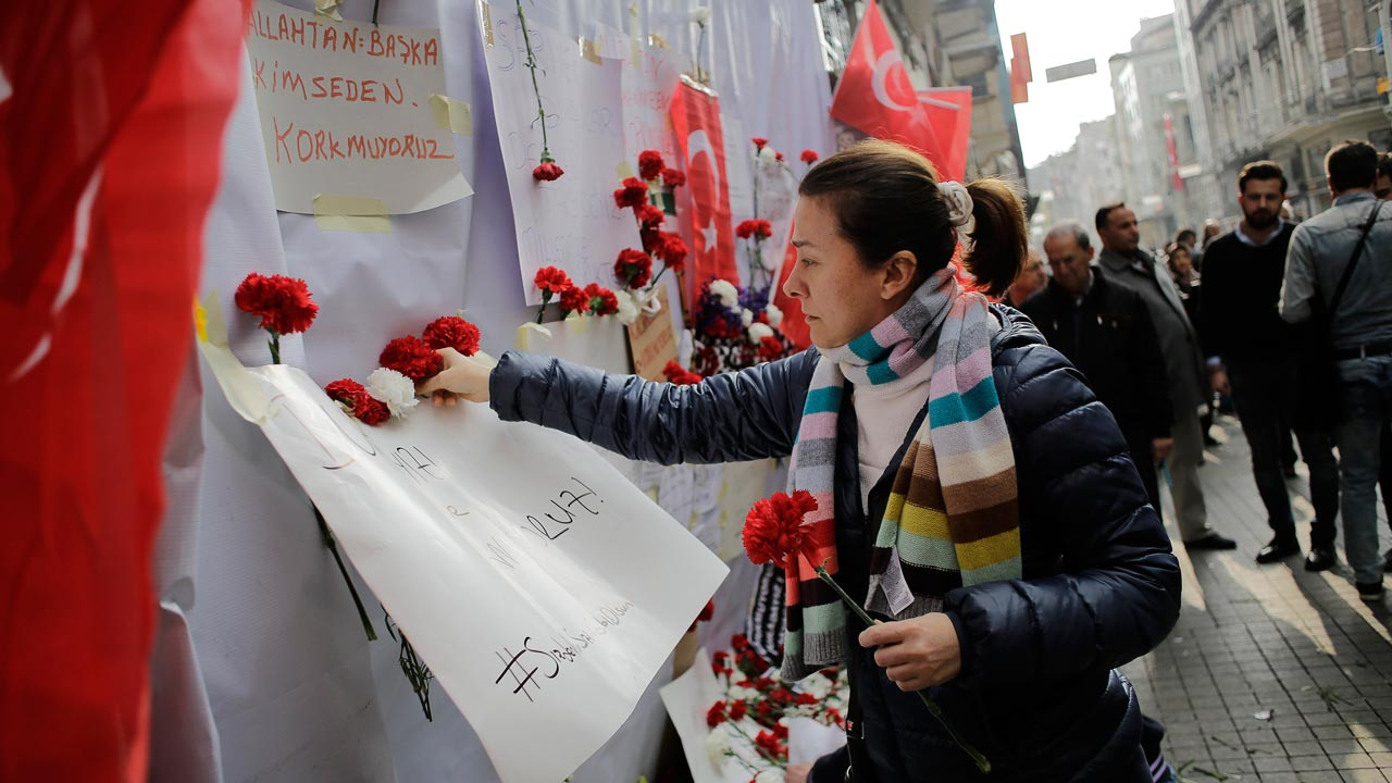 A woman lays flowers on a makeshift memorial at the location of the blast of a suicide attack on Istiklal Street, a major shopping and tourist district, in central Istanbul, on March 20, 2016. Three Israelis and one Iranian were killed, and 39 people injured, when the bomber blew himself up March 19 on Istiklal Street, less than a week after another deadly attack left 35 dead in Ankara. A Turkish jihadist with links to the Islamic State carried out the suicide bombing that killed four foreigners on a major shopping street in Istanbul, Interior Minister Efken Ala said March 20.YASIN AKGUL / AFP