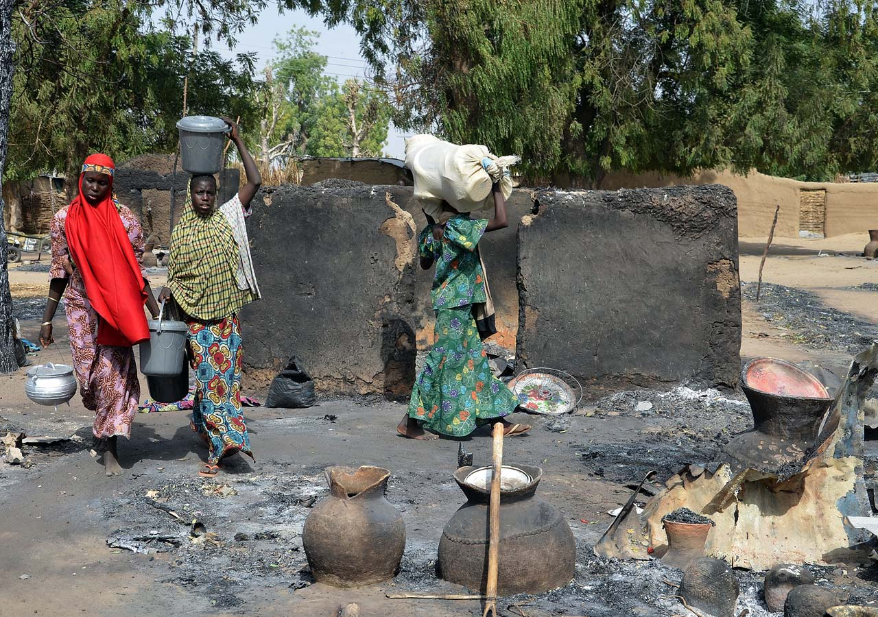 (FILES) This file photo taken on February 06, 2016 at Mairi village outskirts of Maiduguri capital of northeast Borno State, shows young girls fleeing from Boko Haram Islamists walking past burnt house and carrying belongings.   With the Islamists now on the run after a sustained military counter-offensive over the last year, business leaders believe trade should be at the forefront of the region's revival. Fears of raids or the aftermath of deadly attacks have left towns and villages deserted, forcing many in the largely agricultural region into camps for the internally displaced or host communities.  / AFP / STRINGER