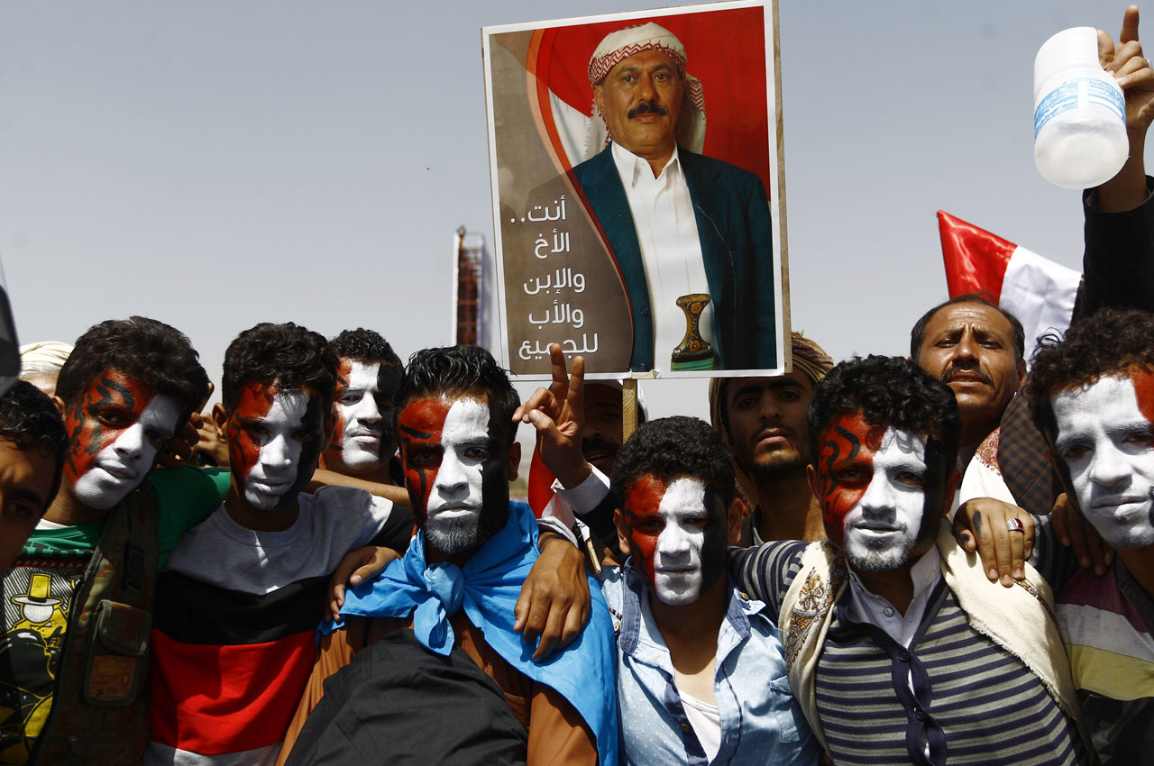 Yemeni protesters hold a placard bearing a portrait of president Ali Abdullah Saleh during a demonstration against the Saudi-led coalition, commemorating one year of the alliance's military campaign against insurgents on March 26, 2016 next to the Monument to the Unknown Soldier in the Yemeni capital Sanaa. The protest was called for by the General People's Congress, the party of rebel-allied former president Ali Abdullah Saleh, who appeared briefly at the rally, an AFP photographer said. The military intervention that began on March 26 last year has yet to deal a decisive blow to the Iran-backed rebels, who continue to control the capital and large parts of the country.  / AFP / MOHAMMED HUWAIS