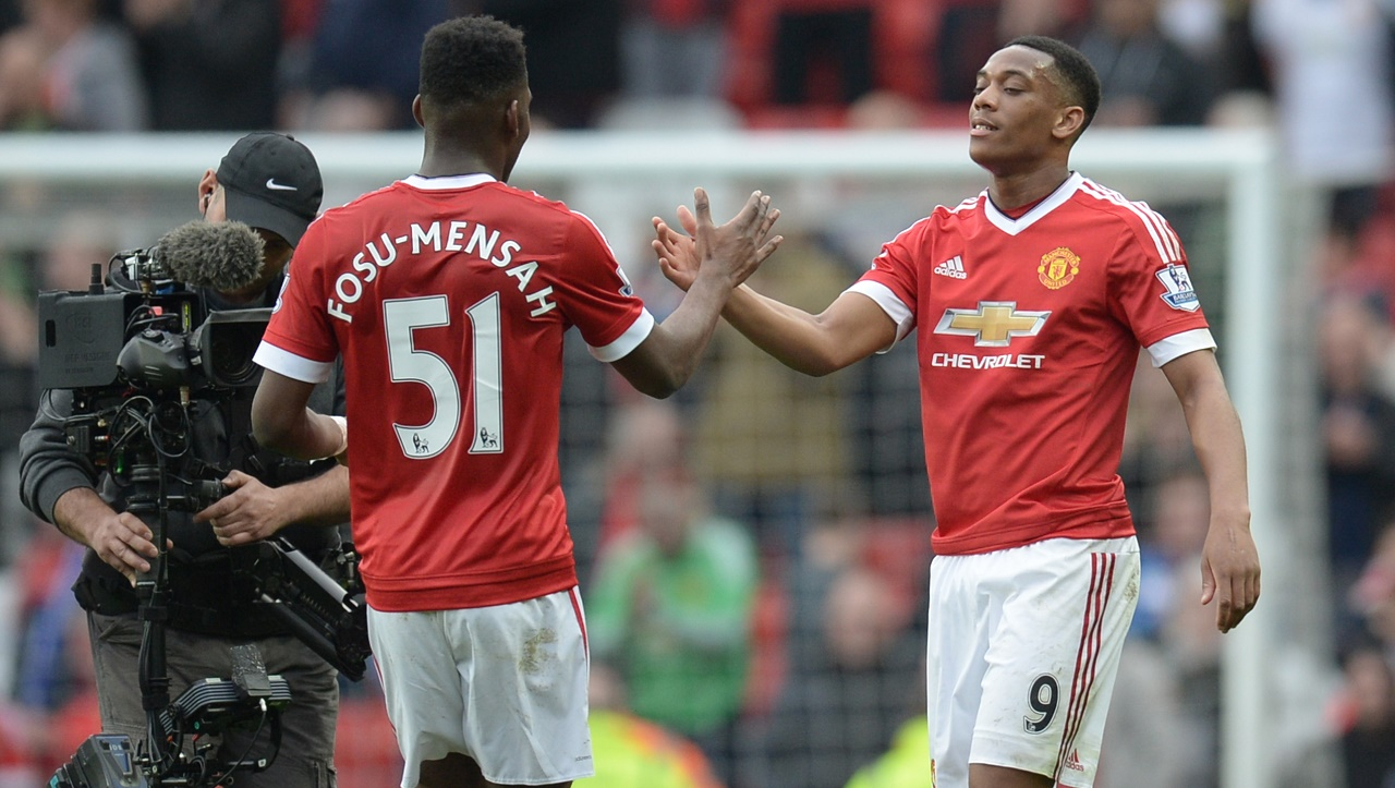 Manchester United's French striker Anthony Martial (R) shakes hands with Manchester United's Dutch defender Timothy Fosu-Mensah (L) at the end of the English Premier League football match between Manchester United and Everton at Old Trafford in Manchester, north west England, on April 3, 2016. / AFP / OLI SCARFF / RESTRICTED TO EDITORIAL USE. No use with unauthorized audio, video, data, fixture lists, club/league logos or 'live' services. Online in-match use limited to 75 images, no video emulation. No use in betting, games or single club/league/player publications. /
