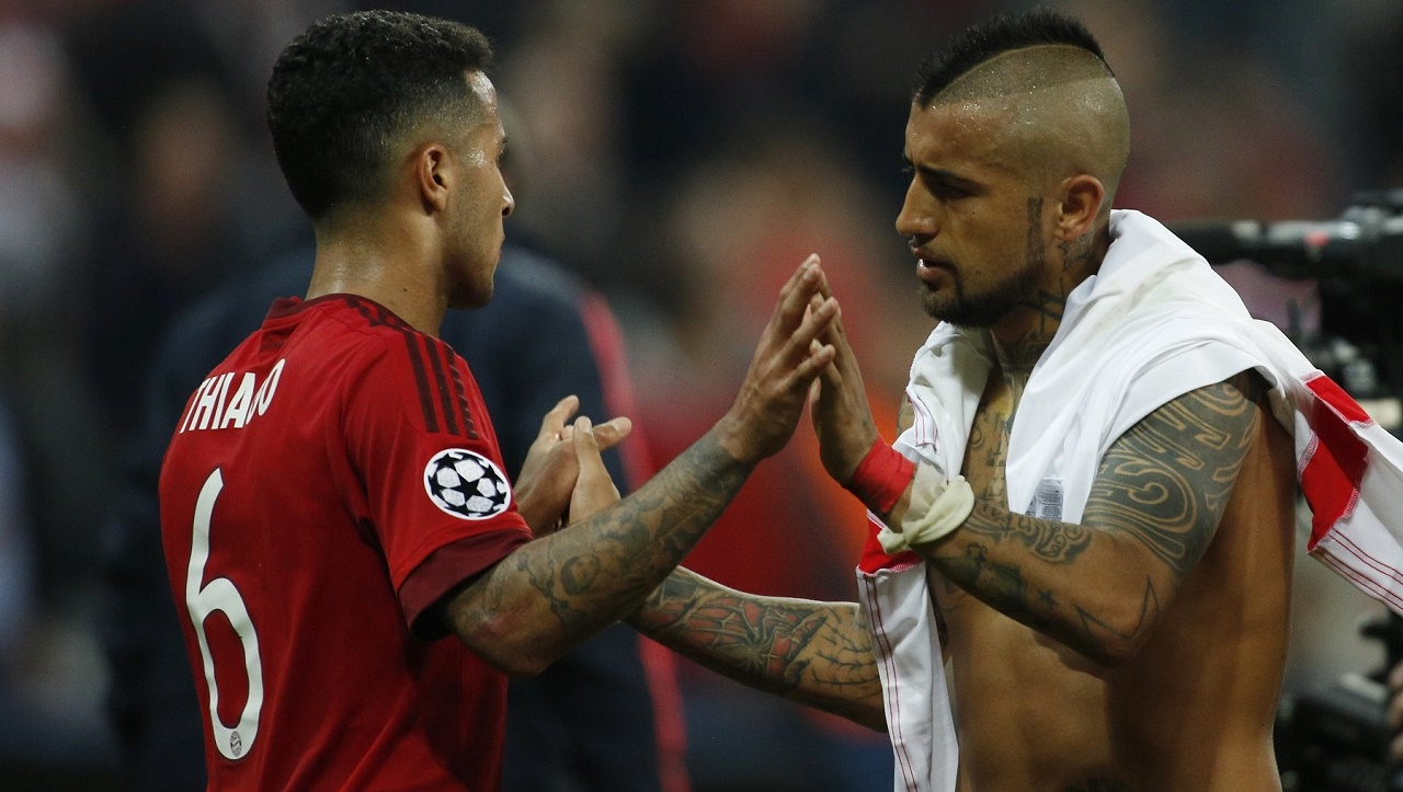 Bayern Munich's Chilean midfielder Arturo Vidal (R) and Bayern Munich's Spanish midfielder Thiago Alcantara celebrate after the Champions League quarter-final, first-leg football match between Bayern Munich and Benfica Lisbon in Munich, southern Germany, on April 5, 2016. Bayern Munich won the match 1-0. / AFP / ODD ANDERSEN