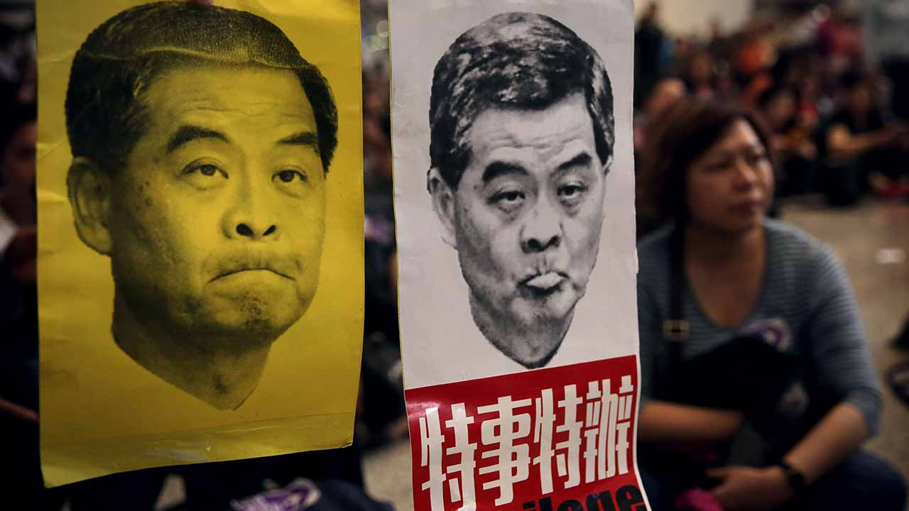 Protesters hold pictures of the city's chief executive Leung Chun-ying during a protest organised by the Hong Kong Cabin Crew Federation at Hong Kong International Airport