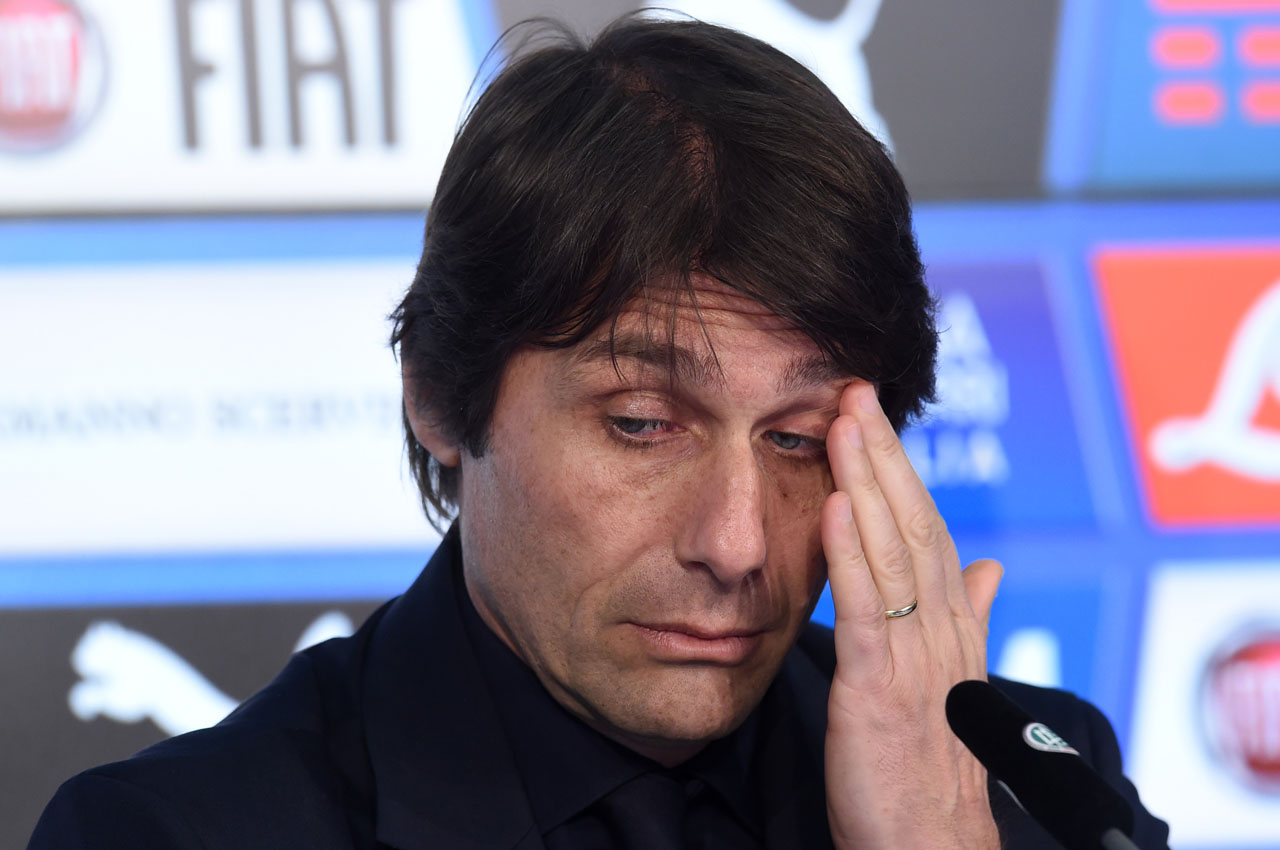 Italian national soccer headcoach Antonio Conte wipes his face during a press conference one day prior the friendly soccer match between Germany and Italy in the stadium in Munich, southern Germany, on March 28, 2016. / AFP / CHRISTOF STACHE