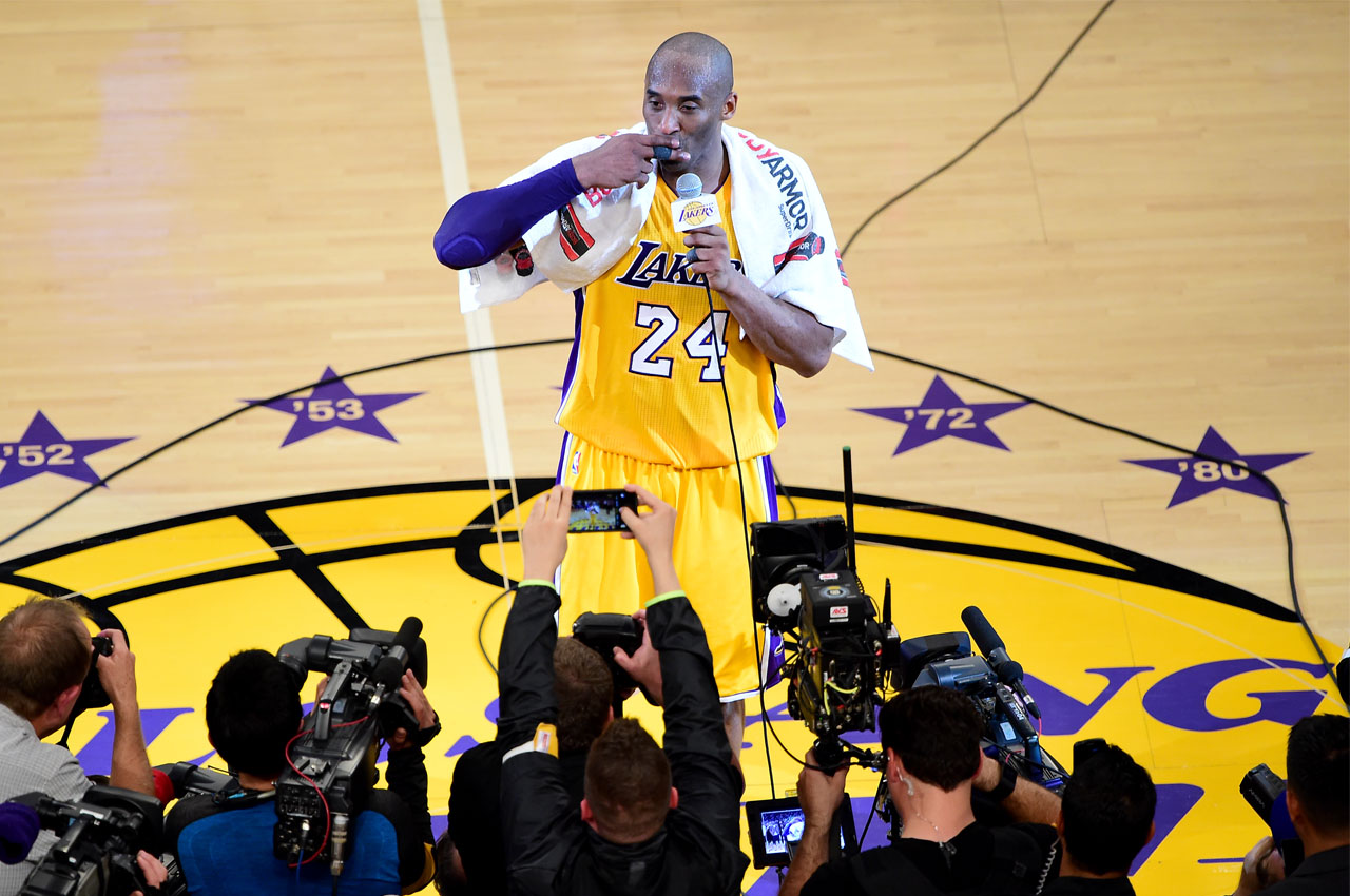 Kobe Bryant (top) of the Los Angeles Lakers reacts while addressing fans following his final game as a Laker in their season-ending NBA western division matchup aginst the Utah Jazz in Los Angeles, California on April 13, 2016, where the Lakers defeated the Jazz 101-96. / AFP PHOTO / FREDERIC J. BROWN