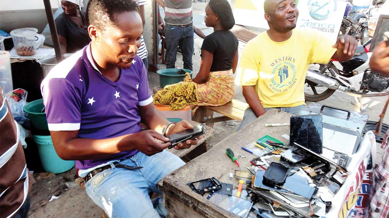 Oluwole, one of the technicians of M&K Technologies repairing phone at Computer Village                                      PHOTO: DEBO OLADIMEJI