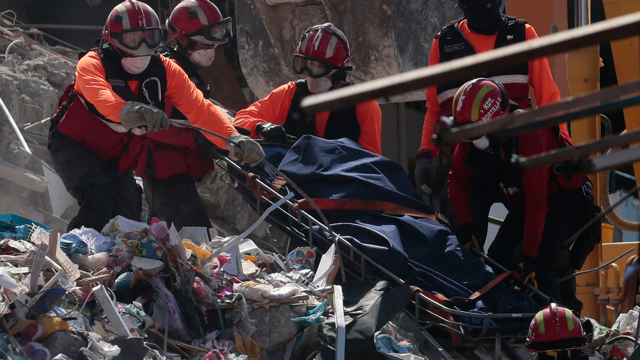 Rescuers remove a corpse from the rubble in Manta, Ecuador on April 20, 2016.  The death toll from Ecuador's earthquake was set to rise sharply after authorities warned that 1,700 people were still missing and anger gripped families of victims trapped in the rubble. A 6.1-magnitude earthquake struck off the coast of Ecuador Wednesday, sowing new panic four days after a more powerful quake killed more than 525 people, with hundreds still missing. / AFP PHOTO / Juan Cevallos