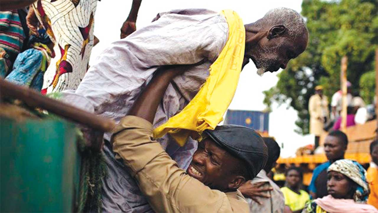 Father Bernard Kinvi helps a Muslim man climb down from an open truck in Bossemptele, Central African Republic. Photograph: Siegfried Modola/Reuters