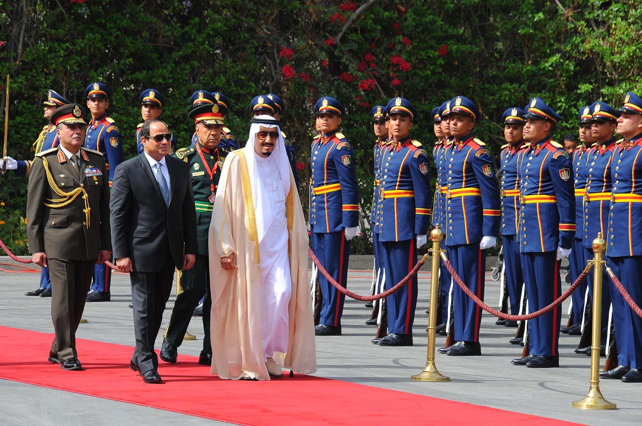 A handout picture released by the Egyptian Presidency on April 7, 2016 shows Egyptian President Abdel Fattah al-Sisi (L) and Saudi King Salman bin Abdulaziz reviewing troops before a meeting in the capital Cairo.  Saudi King Salman started a five-day visit to Cairo in a show of support for Egyptian President Abdel Fattah al-Sisi, with the leaders due to sign a raft of investment deals.  / AFP PHOTO / EGYPTIAN PRESIDENCY AND AFP PHOTO / STRINGER /